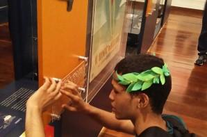 FOTO: Jovem, aluno do ICB, está lendo (em braile) a descrição de um quadro da exposição.