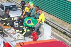 FOTO: Ao centro Os atletas Cassio Reis e Jefinho, seguram a bandeira do Brasil, estão fardados com o uniforme oficial da Seleção Brasileira de Futebol de 5 e estão ao lado de profissionais do ICB. Em um avenida seguem viagem  no carro do Corpo de Bombeiros. (na foto ao lado esquerdo estão três Bombeiros sentados a frente dos atletas)