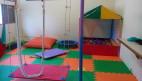 FOTO: A foto mostra a sala de Integração Sensorial do Centro de Apoio Terapêutico. O chão da sala é colorido por um  tatame da cor verde e laranja. Algumas almofadas compõe a foto. Ao centro um aparelho terapêutico semelhante e no canto direito uma piscina de bolas coloridas.