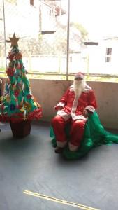 FOTO: Papai Noel ao centro, ao  lado esquerdo  uma Árvore de Natal