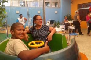 FOTO: Um aluno e uma aluna estão  sentados em um brinquedo animado. Eles estão olhando para foto e sorrindo, o menino acena para a foto.