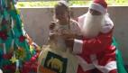FOTO: Ao lado esquerdo uma Árvore de Natal ao lado direito Papai Noel está entregando um presente a uma aluna, a aluna sorri.