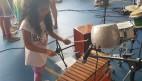 FOTO: Aluna do ICB tocando um instrumento percussivo musical.