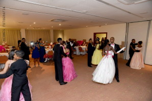 Foto: Ao centro do salão as alunas dançam a valsa com seus pares. Os convidados estão em volta, alguns sentados outros de pé tirando fotos.