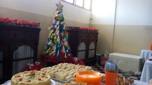 FOTO: A foto mostra os alimentos na mesa principal do buffet.   Ao fundo da foto o foco está para a Árvore de Natal.