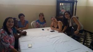 FOTO: A Foto mostra colaboradores sentados a mesa e sorrindo para foto.