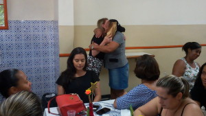 FOTO: A foto mostra a presidenta Sra. Heliana Guimarães Diniz  entregando um presente a uma colaboradora, as duas estão se abraçando.