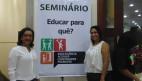 FOTO: Claudia Sampaio a esquerda ao centro um banner escrito - Seminário Educar para que? -  e ao lado direito Tatiane Vieira.