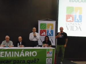FOTO: Uma mesa em auditório estão presentes/sentados as personalidades do evento. De pé com a palavra está o Professor Mauro Brasi.